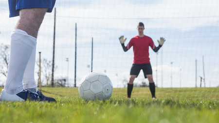 striker: Goalkeeper in red waiting for striker to hit ball on a clear day