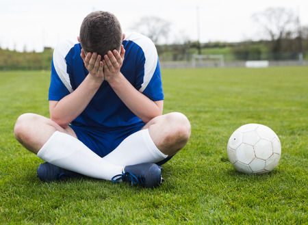 disappointed: Disappointed football player in blue sitting on pitch after losing on a clear day Stock Photo