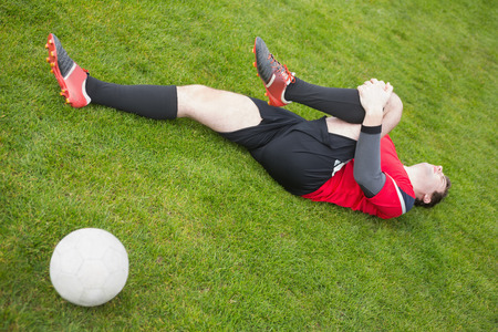 Football player in red lying injured on the pitch on a clear day photo