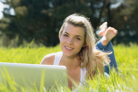 Pretty blonde lying on grass using laptop smiling at camera on a sunny day in the countryside photo