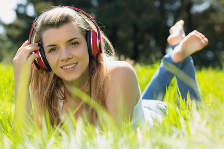 Pretty blonde lying on grass listening to music on a sunny day in the countryside photo
