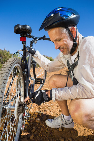 smiing: Smiing cyclist fixing his bike chain on country terrain on a sunny day Stock Photo