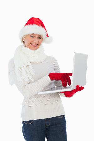 Festive woman using laptop smiling at camera on white background photo