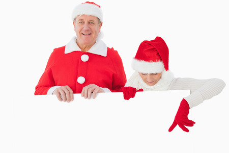 Festive older couple smiling and holding poster on white background photo
