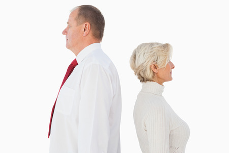 facing each other: Older couple standing not facing each other on white background