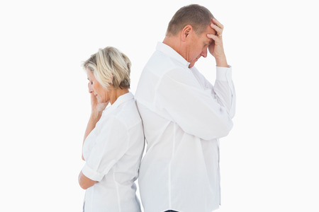 solemn: Upset couple not talking to each other after fight on white background Stock Photo