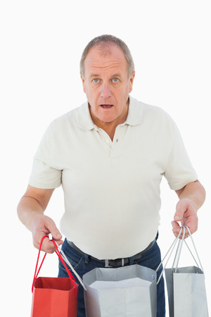 remorse: Mature man feeling buyers remorse holding bags on white background Stock Photo