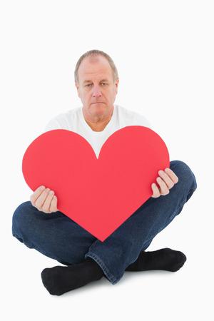 desolaci�n: Malestar hombre sentado la celebraci�n de la forma del coraz�n en el fondo blanco