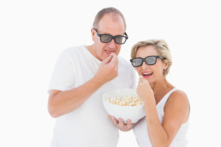 Mature couple wearing 3d glasses eating popcorn on white background photo