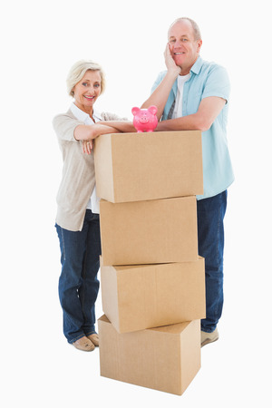 Older couple smiling at camera with moving boxes and piggy bank on white background photo