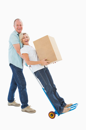Fun older couple holding moving boxes on white background photo