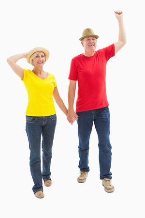 Mature couple walking and holding hands on white background photo