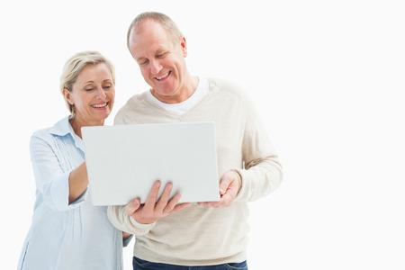 Happy mature couple using laptop on white background photo