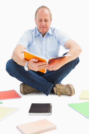 self study: Mature student studying from notebook on white background