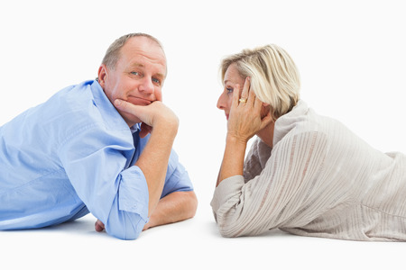 Mature couple lying and smiling on white background photo