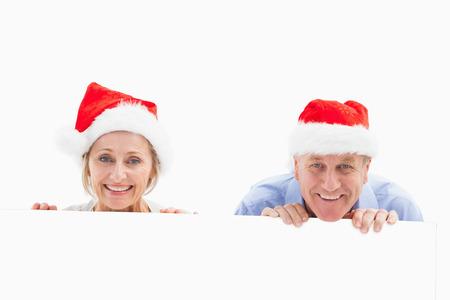 Festive mature couple smiling at camera on white background photo