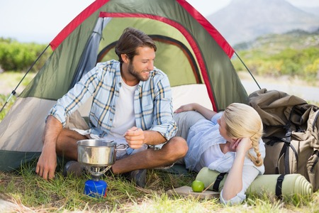 adventuring: Attractive happy couple cooking on camping stove on a sunny day Stock Photo