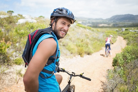 Fit couple cycling on mountain trail man smiling at camera on a sunny day photo