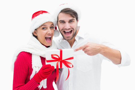Attractive festive couple pointing to present on white background photo
