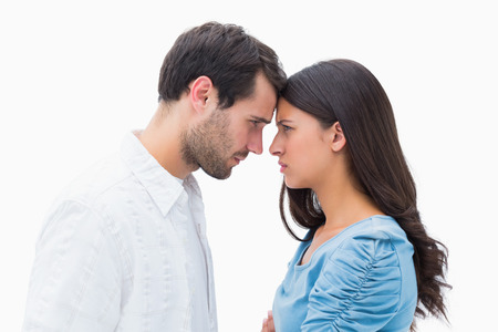 cut off head: Angry couple staring at each other on white background
