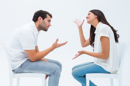 exasperated: Couple sitting on chairs arguing on white background