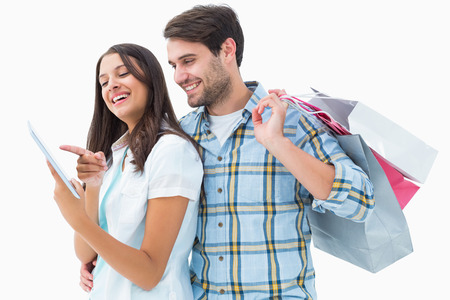 Attractive young couple with shopping bags and tablet pc on white background photo
