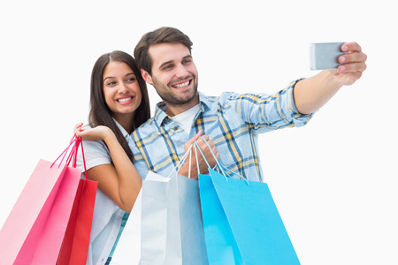 Attractive young couple with shopping bags taking a selfie on white background photo