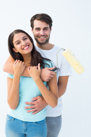 Happy young couple painting together on white background photo