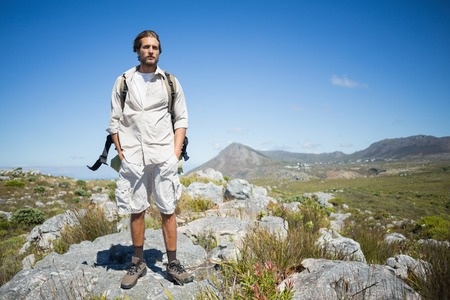 adventuring: Handsome hiker standing at the summit on a sunny day