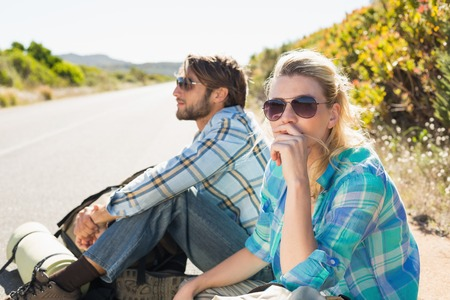 Attractive couple sitting on the road hitch hiking on a sunny day photo