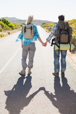 Attractive couple standing on the road holding hands on a sunny day photo