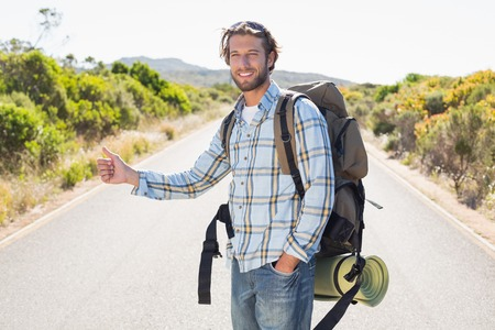 hitch hiker: Attractive man hitch hiking on rural road on a sunny day Stock Photo
