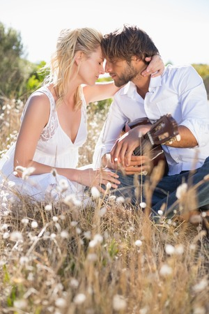 Handsome man serenading his girlfriend with guitar on a sunny day Stock Photo