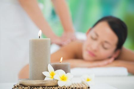 Hermosa morena disfrutando de un masaje de espalda sonriendo a la cámara en un balneario de lujo