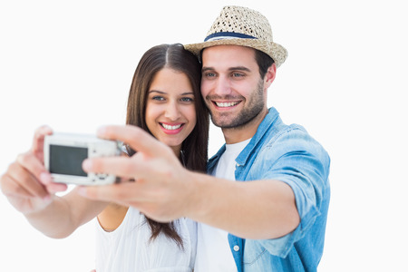 Happy hipster couple taking a selfie on white background photo