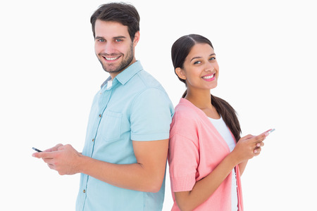Happy couple sending text messages on white background photo