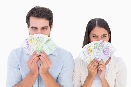 Happy couple showing their money on white background photo