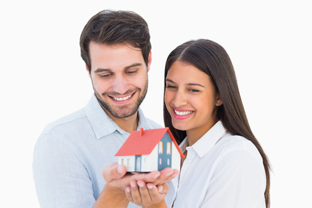 Attractive young couple holding a model house on white background photo