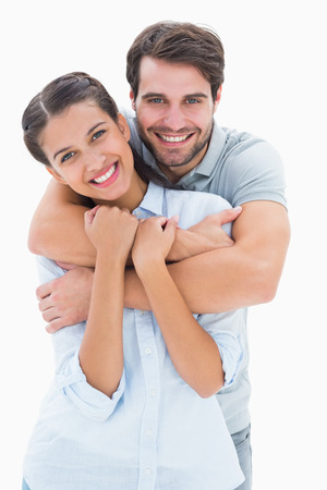 Cute couple smiling at camera on white background photo