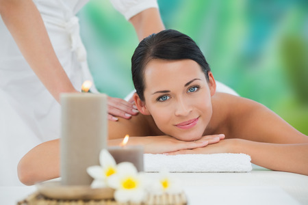 Beautiful brunette enjoying a back massage smiling at camera at a luxury spa photo