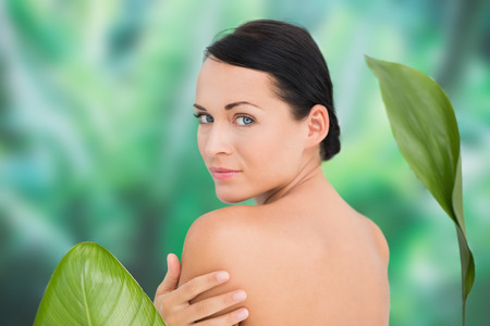 woman naked body: Beautiful nude brunette posing with green leaves on blue and green background