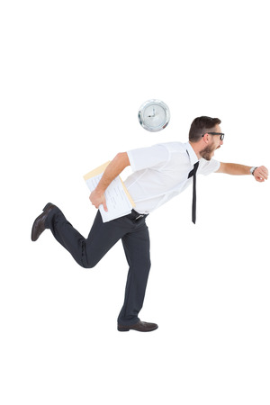 Geeky young businessman running late on white background photo