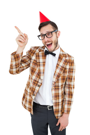 Geeky hipster in party hat pointing on white background Stock Photo