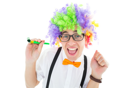 Geeky hipster wearing a rainbow wig holding party horn on white background photo