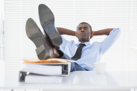 scowl: Relaxed businessman sitting in his chair with feet up in his office Stock Photo