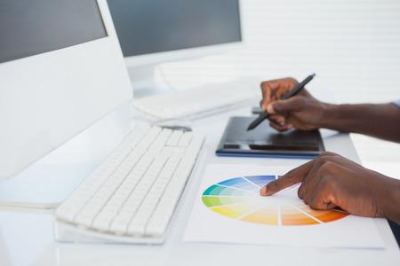 digitizer: Designer sitting at his desk working with digitizer in his office