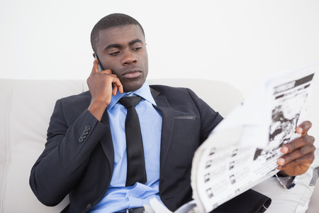 Businessman making a call while reading the paper on sofa at home in the living room photo