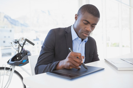 Focused designer drawing on digitizer in his office photo