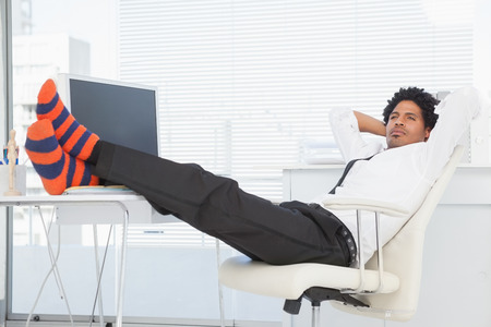 Businessman relaxing in his swivel chair with feet up in his office photo