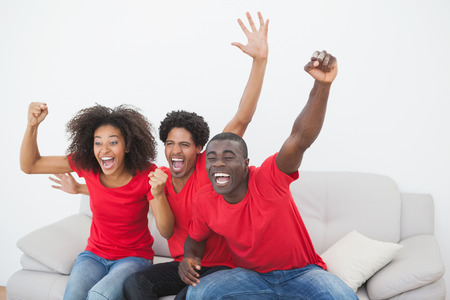 Football fans sitting on couch cheering together at home in the living room photo